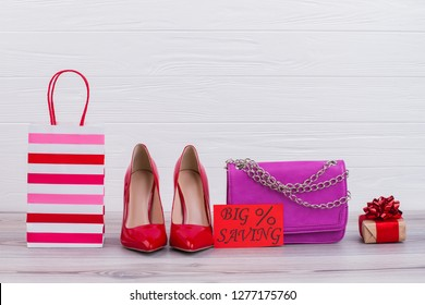 Female accessories and card with inscription big saving. Female high heels, chain leather bag and gift box on wooden background. Womens fashion sale.