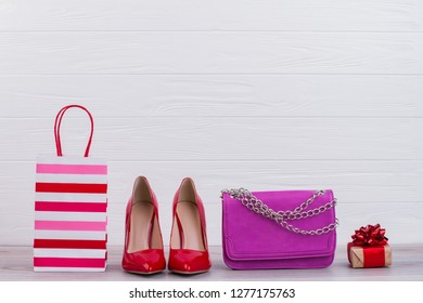 Female accessories and shopping bag. Female lacquered heels, leather handbag, paper bag and present box. Womens Day sale.