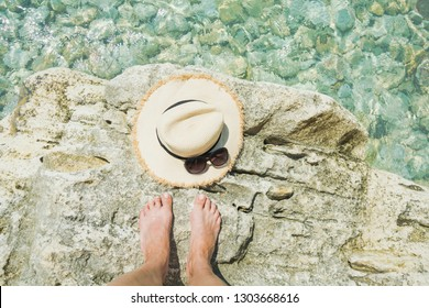 Female accessory, straw sunhat, glasses and long legs on big stone. Clear sea. Summer vacation. Wild beach.