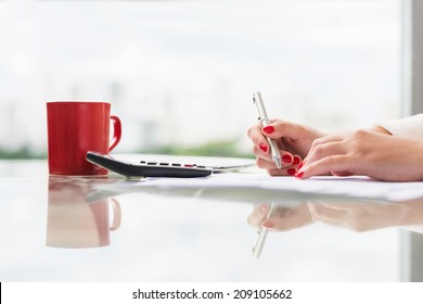 Female accountant signing a document, side view