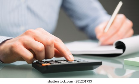 A female accountant uses a calculator and takes notes on a paper notebook on an office desk.