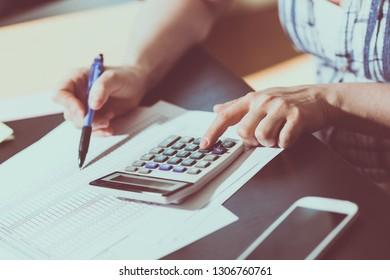 Female accountant using calculator in office