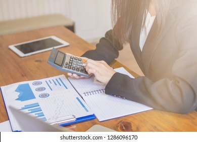 Female accountants are using a calculator to summarize the amount of income, expenditure and annual statistics to summarize business results. Accountants are using calculators for accurate results.
