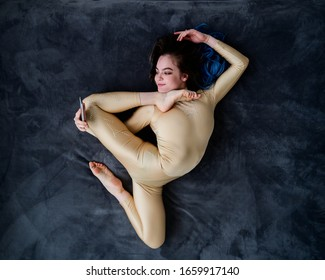 A female acrobat lies on a gray bedspread in a curved pose and uses a mobile. A woman contortionist resting on a bed in an acrobatic stunt and texting on the phone.