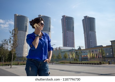 Female active lifestyle in the megalopolis. The girl speaks on a mobile phone on a background of buildings.