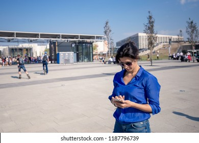 Female active lifestyle in the megalopolis. The girl speaks on a mobile phone on a background of people in the park.