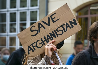 Female activist holding a cardboard sign with text Safe Afghanistan at a demonstration in Lubeck, Germany after the Taliban takeover, selected focus