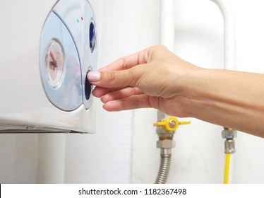 Female adjusting a central heating gas boiler at home.