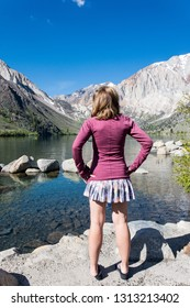 Female adult stands by Convict Lake in the springtime, located off of US-395, near Mammoth Lakes California in the eastern Sierra Nevada mountains, Inyo National Forest.