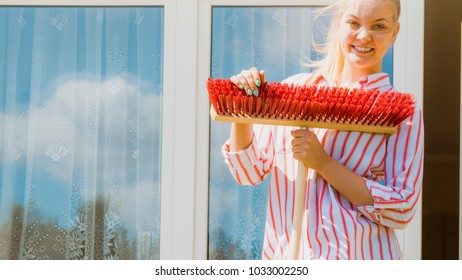 Female adult young woman using big broom to clean up backyard patio