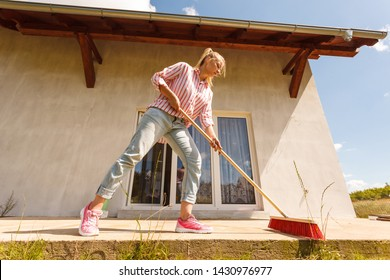 Female adult young woman using big broom to clean up backyard patio. Housecare duties concept.