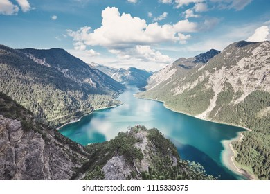 Female adventurer with backpack exploring valley from top of mountain enjoying beautiful view to summer lake with turquoise water - adventure, travel and hiking concept. Plansee, Austria