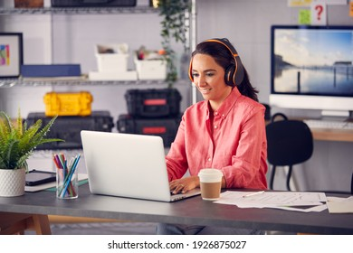Female Advertising Marketing Or Design Creative With Wireless Headphones At Desk Working On Laptop