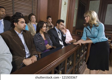 Female advocate talking to the jurors sitting in witness stand at courthouse