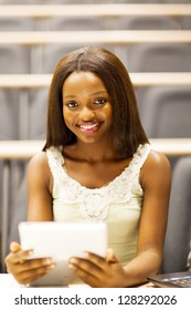 female african college student using tablet computer in lecture room