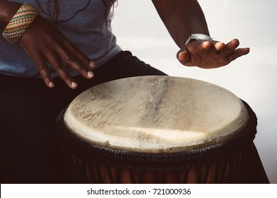 A female african musician plays the djembe drum. She is against a white background.