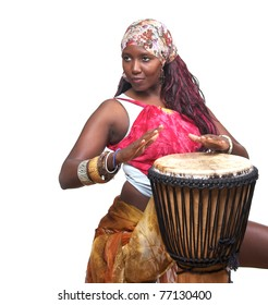 A female african musician plays the djembe drum.  She is isolated against a white background.