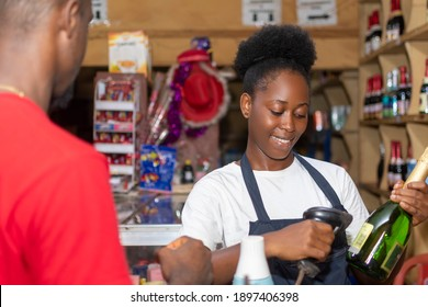 female african sales woman attending to a customer, checking out the items he bought, using a bar code scanner at the point of purchase