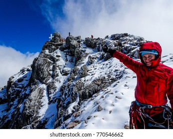 Female alpinist pointing to the summit of Dachstein, the highest peak of the regions styria and upper austria in the Austrian alps, all covered with snow and ice and a white cross in the background