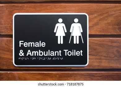 female and Ambulant Toilet sign with wooden background
