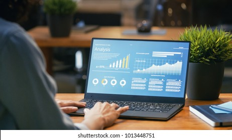 Female Analyst at Her Desk Works on a Laptop Showing Statistics, Graphs and Charts. She Works on the Wooden Table in Creative Office. Over the Shoulder Footage.