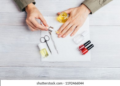 Female apply nourishing oil on cuticles among instruments for manicure, bottles of red varnish and base, top view on white table. Young woman caring of her hands making moisturizing treatments.