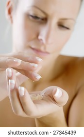 female applying body lotion, only hands in focus