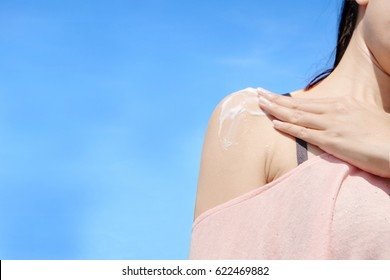 Female applying sunscreen. Very sun light Sky background.