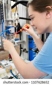 Female Apprentice Engineer Working On Machine In Factory