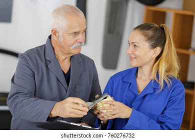 female apprentice mechanic working with teacher