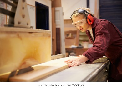 Female Apprentice Using Circular Saw In Carpentry Workshop
