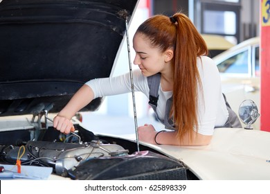 Female apprentice working on a car engine with wrench