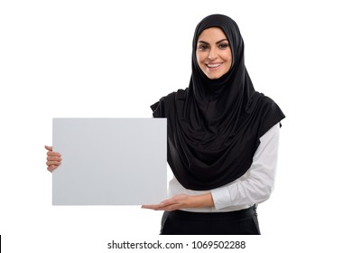Female Arabian office worker holding a blank placard. Joyful mood and happy face. Success at work.