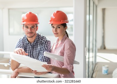 A female architect and a foreman examining blueprints on a construction site. they are standing in a luminous open space, leaning against a white guardrail. They are wearing orange hard hats