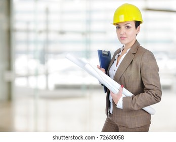 Female architect holding blueprints with helmet on head
