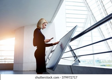 Female architect holding cell telephone while viewing 3d-visualization of project on digital touch screen, woman preparing a presentation for staff via high tech computer display and mobile phone