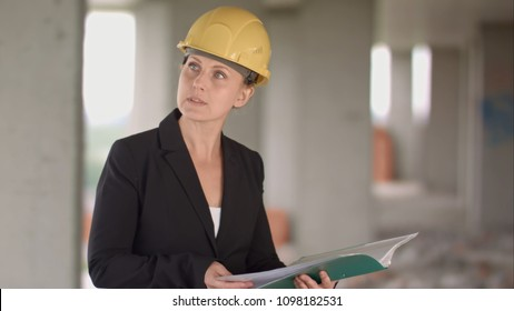 Female architect looking at blueprints at construction site