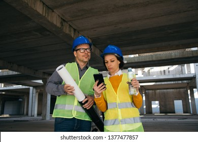 Female architect showing blueprint on her smart phone to her colleague