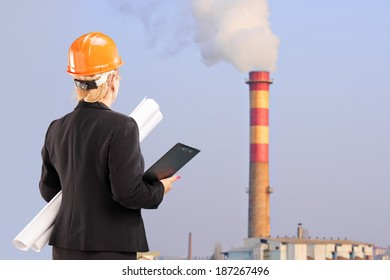 Female architect standing near a factory outdoors
