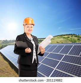 Female architect standing next to solar panels in field shot with tilt and shift lens