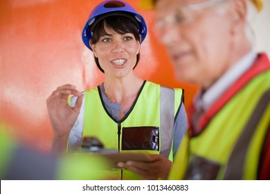 Female architect talking to builders