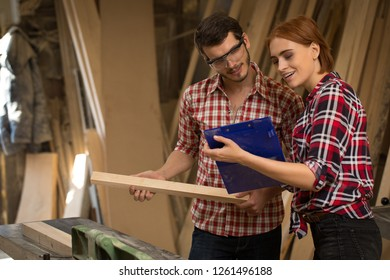Female architect talking with joiner in joiner's shop. Beautiful woman with ginger hair holding blue folder and smiling. Confident carpenter holding timber and looking at folder.