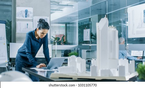 Female Architectural Designer Works on a Laptop,  Engineering New Building Model for the Urban Planning Project. Clean Minimalistic Office, Concrete Walls Covered by Blueprints and Documents.