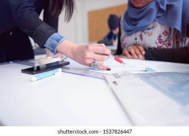 Female Architecture teacher at work. Female professor explain architectural projects to students. Beautiful female university architecture professor explain lessons to multiethnic students.
