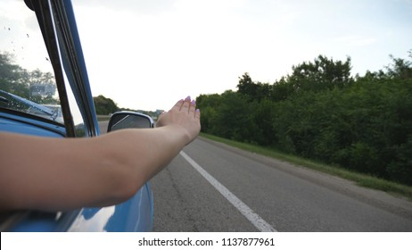 Female arm outside of retro car playing with wind during summer trip. Young woman waving with her hand in wind at travel. Girl puts her arm out the window of old car to feel the breeze. Slow motion.