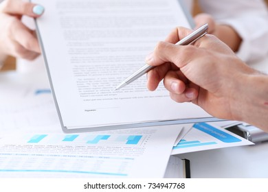Female arm in suit offer contract form on clipboard pad and silver pen to sign closeup. Strike a bargain for profit white collar motivation union decision corporate sale insurance agent concept