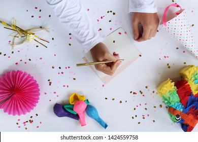 Female arms and hands writing on notecards with birthday decoration objects.