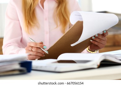 Female arms hold silver pen and pad with financial statistics at workplace closeup. White collar check money papers, school or college homework exercise, internal Revenue Service inspector concept