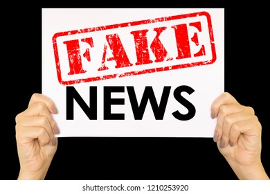 Female arms holding card written  Fake News on black background