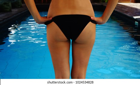 Female arse in front of the pool. Sexy model ass in bikini.